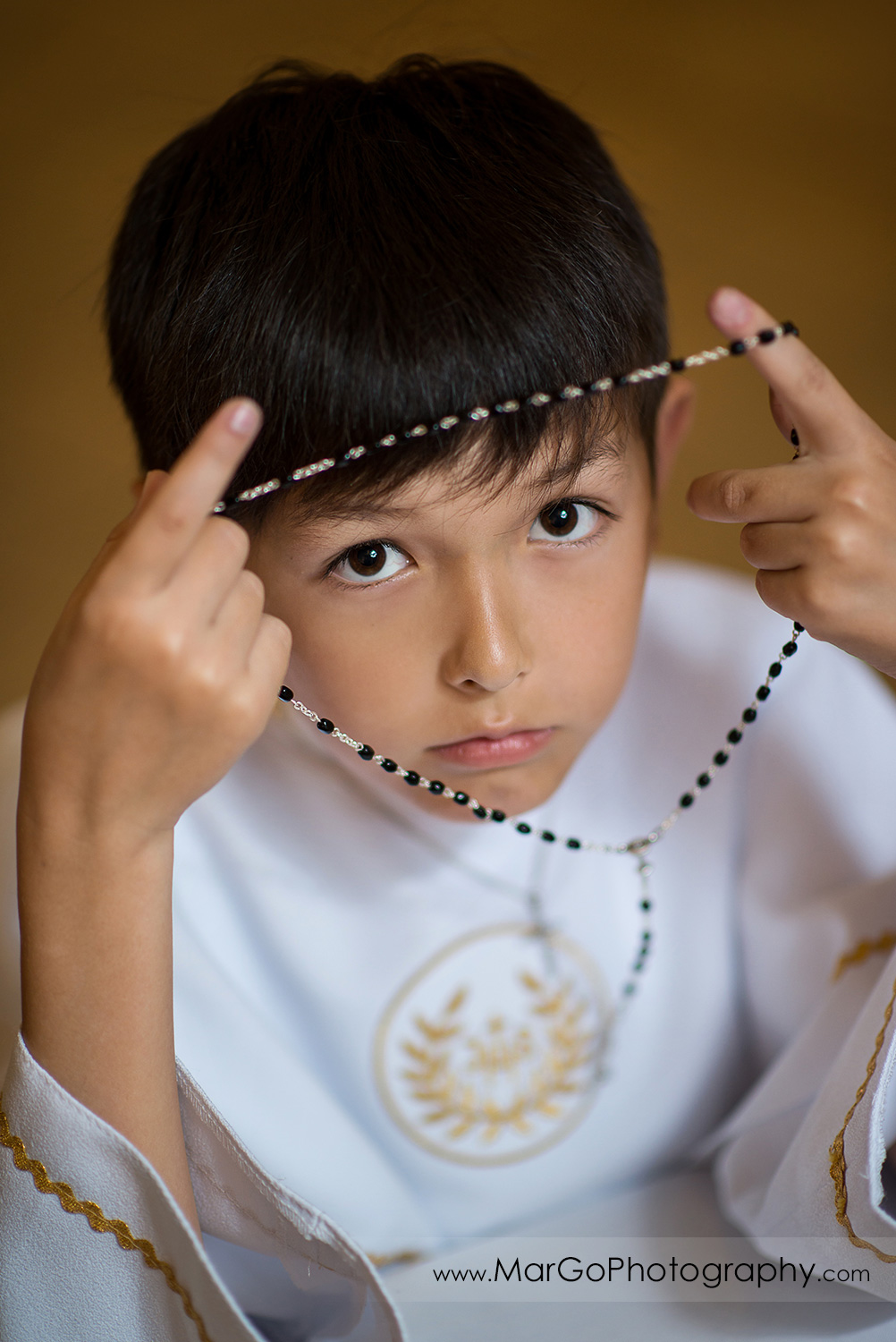 first communion boy in white alb looking through rosary in wooden San Jose church pews