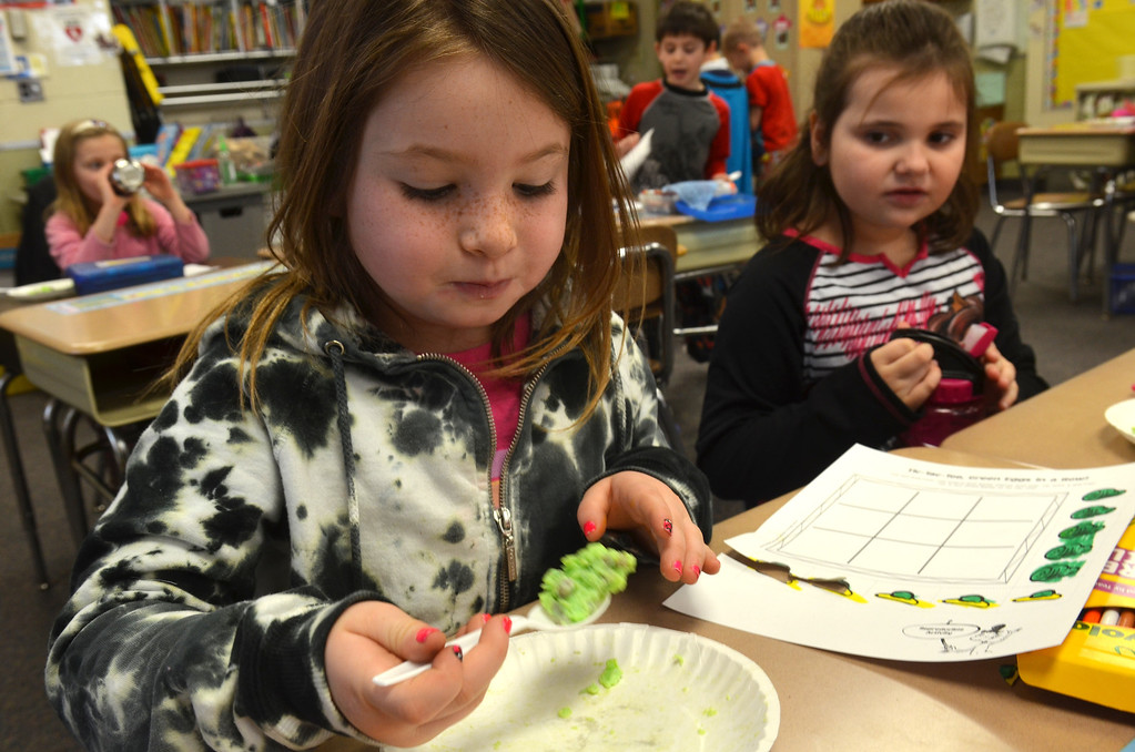 . First grader Elle Stern sample green eggs and ham in a classroom at Montgomery Elementary School.   The snack was served as part of Reading Week activity held annually to celebrate Dr. Seuss\'s birthday.    Friday, March 7, 2014.   Photo by Geoff Patton