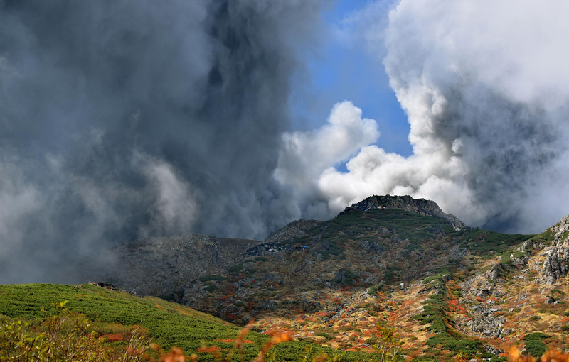 . In this photo taken by an anonymous climber and was offered to Kyodo News, dense plumes rising from the summit crater of Mount Ontake cover the slope carpeted by colored autumn leaves after the volcanic mountain erupted in central Japan, Saturday, Sept. 27, 2014. With a sound likened to thunder, the 3,067-meter (10,062-foot) mountain spewed large white plumes high into the sky, sending people fleeing, covering surrounding areas in ash, injuring many climbers who were stranded in mountain lodges and areas that rescue workers have been unable to reach.  (AP Photo/Kyodo News)