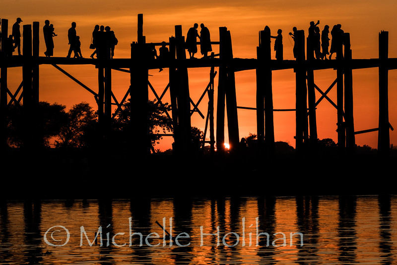 Monks and tourists gather on U-Bein Bridge at sunset in Mandalay, Myanmar