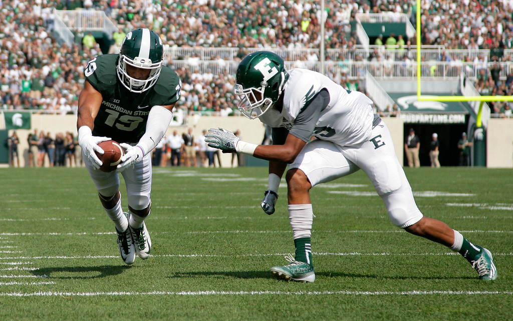 . Michigan State receiver A.J. Troup, left, dives for a touchdown against Eastern Michigan\'s Jason Beck during the second quarter of an NCAA college football game, Saturday, Sept. 20, 2014, in East Lansing, Mich. Michigan State won 73-14. (AP Photo/Al Goldis)
