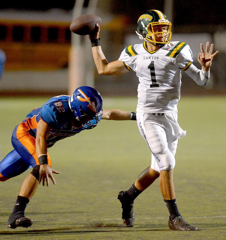 . Canyon High School\'s quarterback Cade Apsay gets a pass off under pressure from Christopher Klifman of Westlake High August 30, 2013 in Westlake Village, CA.(Andy Holzman/Los Angeles Daily News)