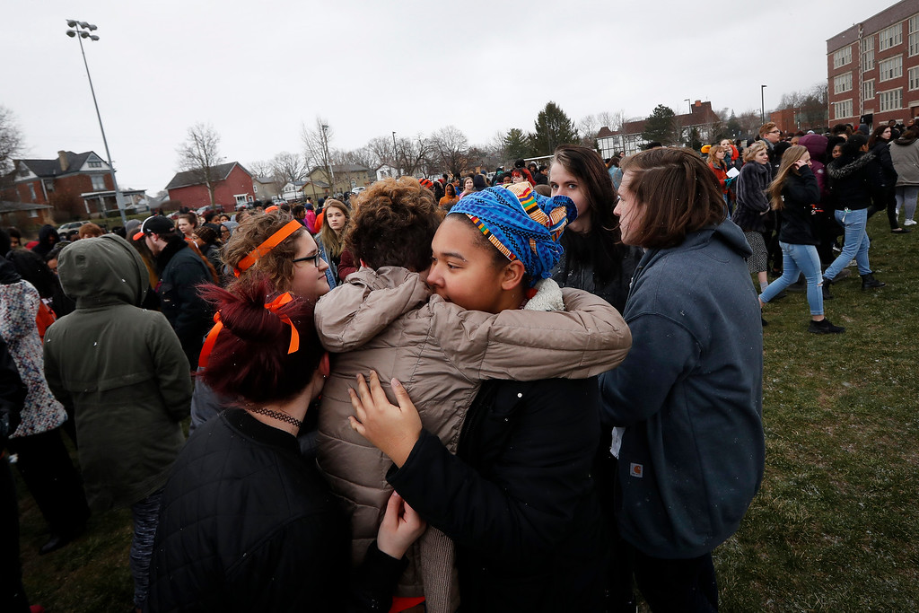 . Students embrace as they gather on their soccer field during a 17-minute walkout protest at the Stivers School for the Arts, Wednesday, March 14, 2018, in Dayton, Ohio. Students across the country participated in walkouts Wednesday to protest gun violence, one month after the deadly shooting inside a high school in Parkland, Fla. (AP Photo/John Minchillo)