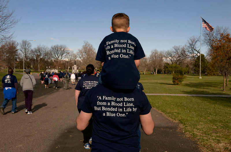 . Five-year-old Brayden Karlen sits on top of his father\'s shoulders.  His father, Josh Karlen, is a police officer with Thornton Police Department.  Family, colleagues, and friends of slain Denver Police Officer Celena Hollis turned out April 7, 2013 for a 5k run and walk to raise money for a scholarship fun and a memorial bench in City Park in Denver, CO.  Over 300 runners and walkers participated in the race that started at 9:00 am.  The race looped around City Park.  After the race, a gathering was held to remember Hollis and 22 white doves were released in her memory.  (Photo By Helen H. Richardson/ The Denver Post)