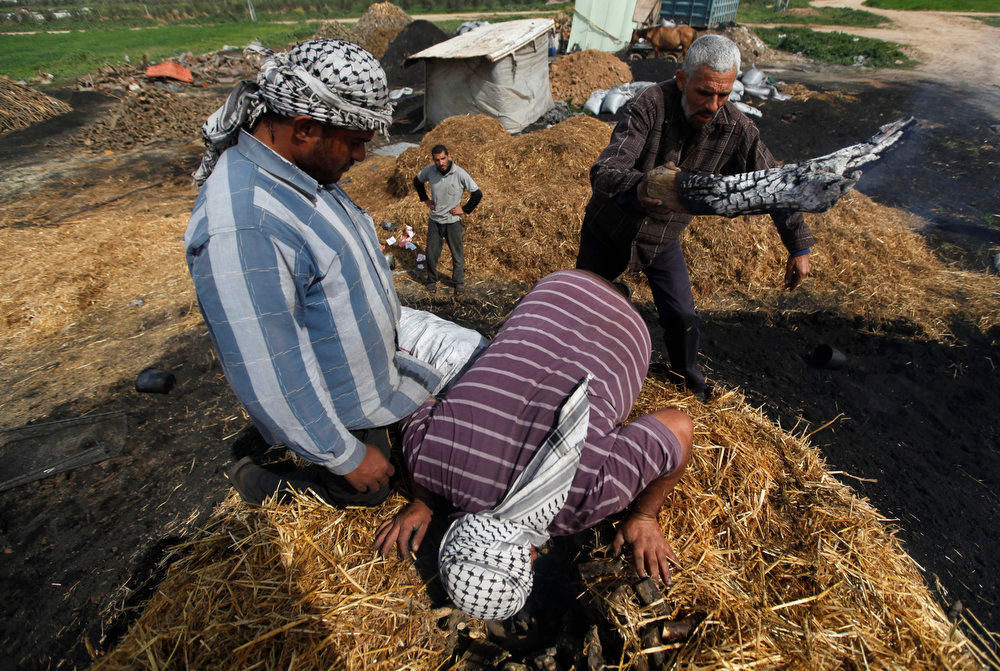 . A Palestinian worker places embers on wood to be burned and turned into coal at one of the few local charcoal manufacturing shops east of Gaza City on Feb. 25, 2013. In adapting to years of border blockades and shortages, Gazans have become experts at recycling and making new out of old, including turning scrap wood into charcoal being used for barbecue grills and water pipes in local restaurants and coffee houses.(AP Photo/Hatem Moussa)