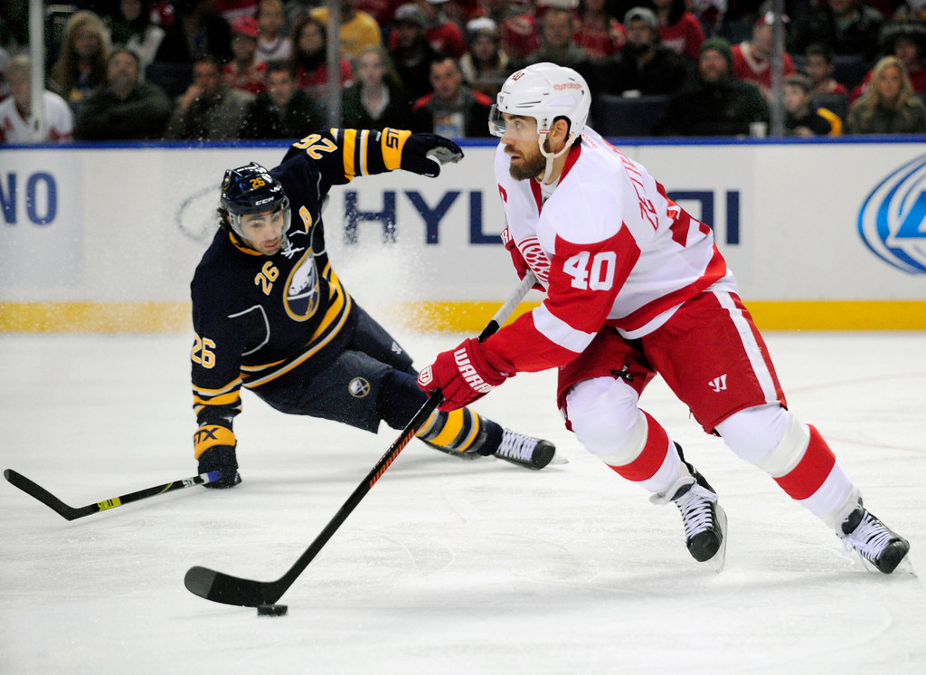. Buffalo Sabres left winger Matt Moulson (26) battles for the puck as Detroit Red Wings left winger Henrik Zetterberg (40), of Sweden, carries the puck up ice during the first period of an NHL hockey game Sunday, Nov. 2, 2014, in Buffalo, N.Y. (AP Photo/Gary Wiepert)