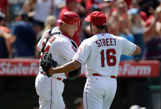 . Los Angeles Angels catcher Hank Conger, left, and relief pitcher Huston Street celebrate their 2-1 win over the Detroit Tigers in a baseball game on Sunday, July 27, 2014, in Anaheim, Calif. (AP Photo/Jae C. Hong)