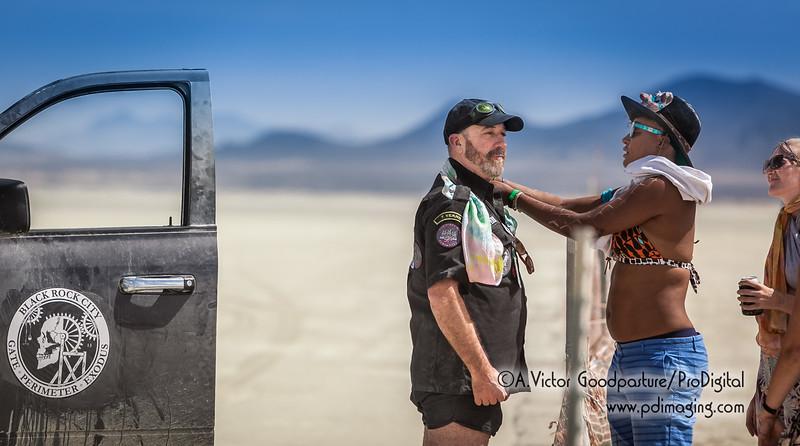 A burner gives a volunteer ranger a tie dye scarf.