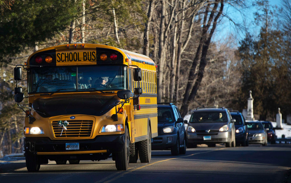 Description of . A school bus carrying children from Sandy Hook Elementary School makes its way to their new school in Monroe as they leave Newtown, Connecticut January 3, 2013. Hundreds of the children who escaped the harrowing attack on their elementary school in Newtown, Connecticut, last month head back to classes on Thursday for the first time since a gunman killed 20 of their schoolmates and six staff members. School officials are preparing for droves of anxious parents to join the fleet of buses carting children to a disused middle school in the neighboring town of Monroe. REUTERS/Shannon Stapleton