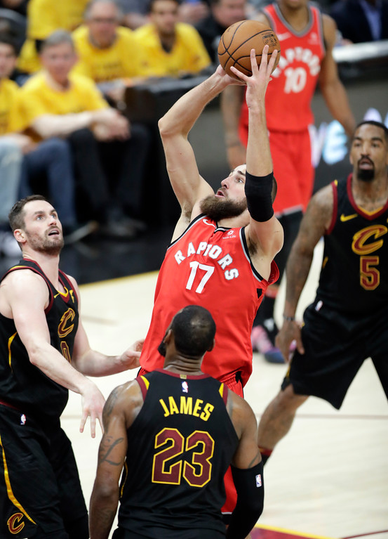 . Toronto Raptors\' Jonas Valanciunas (17), from Lithuania, shoots between Cleveland Cavaliers\' Kevin Love, left, LeBron James (23) and JR Smith (5) in the second half of Game 4 of an NBA basketball second-round playoff series, Monday, May 7, 2018, in Cleveland. (AP Photo/Tony Dejak)