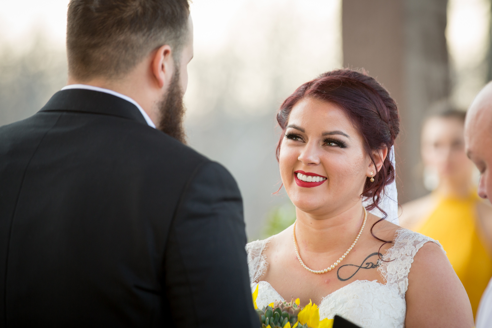 a bride looking at her groom at the altar as they are getting married