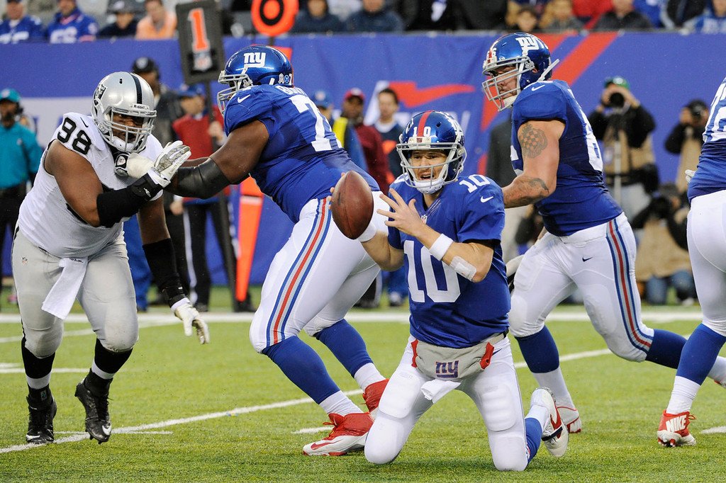 . New York Giants quarterback Eli Manning (10) falls to his knees while trying to avoid being hit during the first half of an NFL football game against the Oakland Raiders, Sunday, Nov. 10, 2013, in East Rutherford, N.J. (AP Photo/Bill Kostroun)