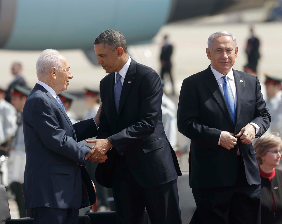. President Barack Obama, center, shakes hands with Israeli President Shimon Peres , left, while on stage with Israeli Prime Minister Benjamin Netanyahu, right, during his arrival ceremony at Ben Gurion International Airport in Tel Aviv, Israel, Wednesday, March 20, 2013, (AP Photo/Pablo Martinez Monsivais)