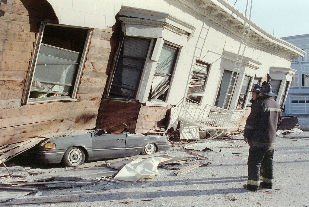 . Two firemen watch, in San Francisco, 18 October 1989, a collapsed house that crushed a car in the Marina District, one of the areas worst hit by an earthquake estimated at 6.9 on the Richter scale that rocked California 17 October 1989.  (ADAM TEITELBAUM/AFP/Getty Images)