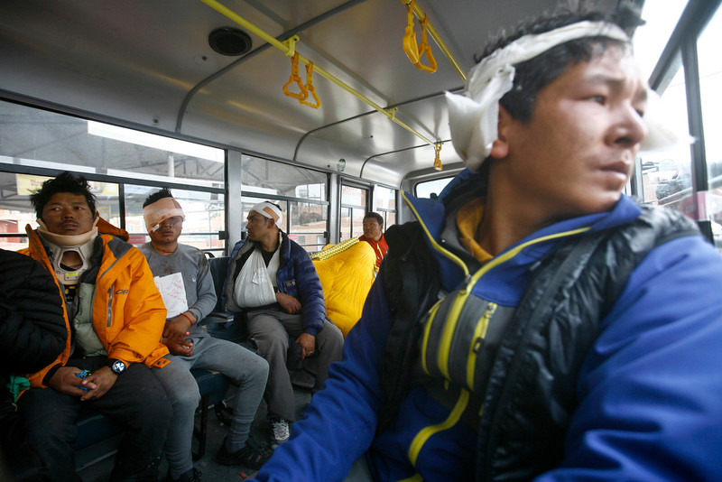 . Injured Sherpa guides sit inside a bus after they were evacuated from Mount Everest Base Camp, in Kathmandu, Nepal, Sunday, April 26, 2015. The first group of survivors from an earthquake-triggered avalanche that swept through the Mount Everest base camp were flown to Nepal\'s capital on Sunday and taken to hospitals. Of those evacuated, 12 were Nepalese Sherpas. (AP Photo/Bikram Rai)