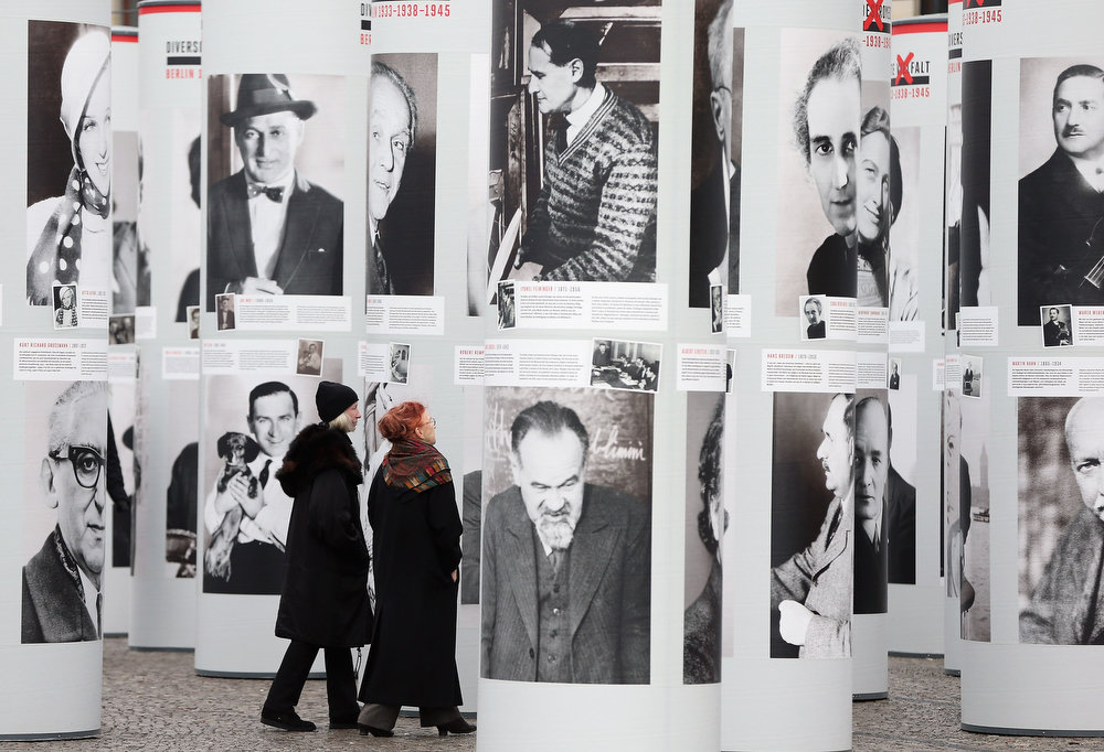 Description of . Visitors walk among portraits of Berlin Jews and political opponents persecuted, and in many cases murdered or driven to suicide, by the Nazis in the exhibition