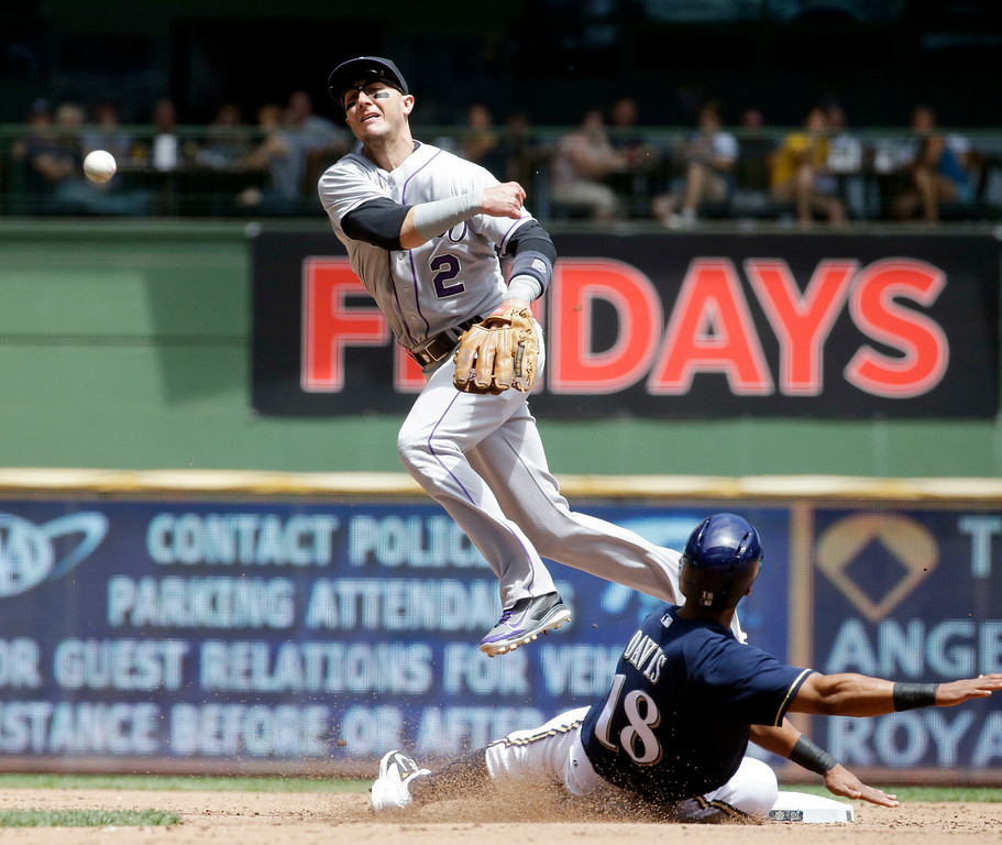 . Milwaukee Brewers\' Khris Davis is out at second as Colorado Rockies\' Troy Tulowitzki turns a double play on a ball hit by Mark Reynolds during the second inning of a baseball game Sunday, June 29, 2014, in Milwaukee. (AP Photo/Morry Gash)