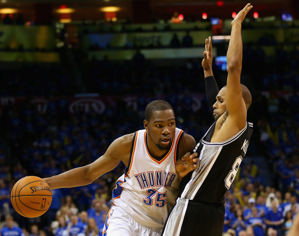 . OKLAHOMA CITY, OK - MAY 25: Kevin Durant #35 of the Oklahoma City Thunder handles the ball against Patty Mills #8 of the San Antonio Spurs in the second half during Game Three of the Western Conference Finals of the 2014 NBA Playoffs at Chesapeake Energy Arena on May 25, 2014 in Oklahoma City, Oklahoma.  (Photo by Ronald Martinez/Getty Images)