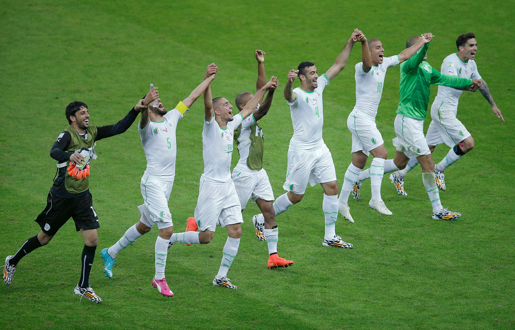 . Members of the Algerian soccer team join hands as they celebrate on the pitch after winning 4-2 , the group H World Cup soccer match between South Korea and Algeria at the Estadio Beira-Rio in Porto Alegre, Brazil, Sunday, June 22, 2014. (AP Photo/Michael Sohn)
