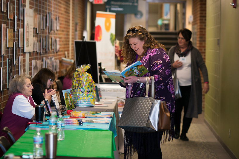 "LANCASTER, OHIO   MARCH 23, 2018: Miranda West, who works in the Legal Affairs Office at Ohio University Athens Campus, looks over a book called ""Bunny Bob"" before purchasing it from author Sandi Latimer at her table during the Celebrate Women Conference 2018, themed ""Recognizing Our Superpowers"" on March 23, 2018 at Ohio University Lancaster in Lancaster, Ohio.  Ty Wright photo"