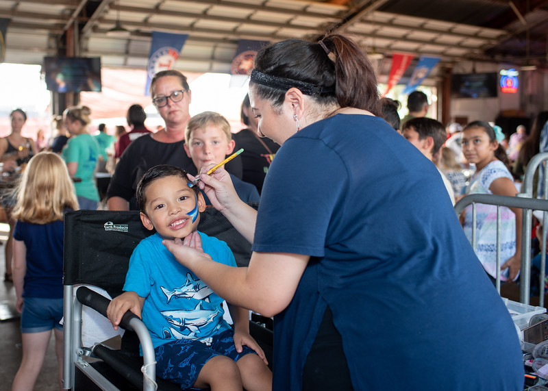 Elijah Murillo gets his face painted during Shark Week Live at Brewster Street Icehouse.