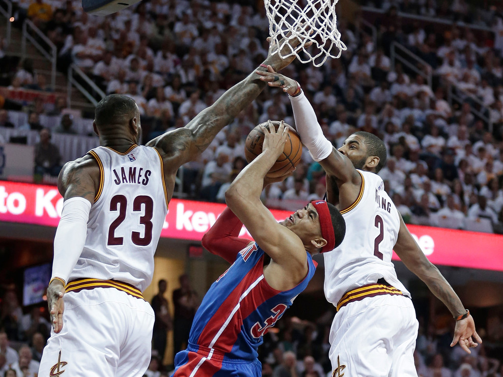 . Detroit Pistons\' Tobias Harris (34) drives to the basket against Cleveland Cavaliers\' LeBron James (23) and Kyrie Irving (2) in the second half in Game 1 of a first-round NBA basketball playoff series, Sunday, April 17, 2016, in Cleveland. The Cavaliers won 106-101. (AP Photo/Tony Dejak)