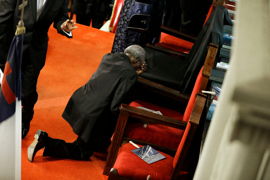 . A parishioner prays at the empty seat of the Rev. Clementa Pinckney at the Emanuel A.M.E. Church four days after a mass shooting that claimed the lives of Pinckney and eight others on Sunday, June 21, 2015, in Charleston, S.C. (AP Photo/David Goldman, Pool)