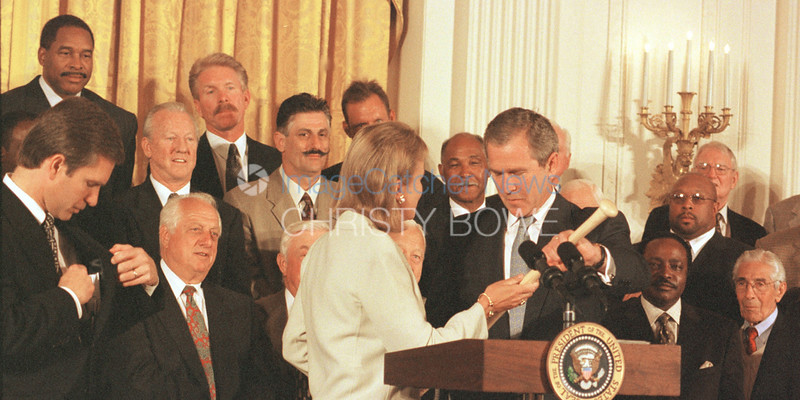 President Bush is awarded a baseball bat signed by all of the living hall of famers in the East Room of the White House as they celebrate the opening of the baseball season.