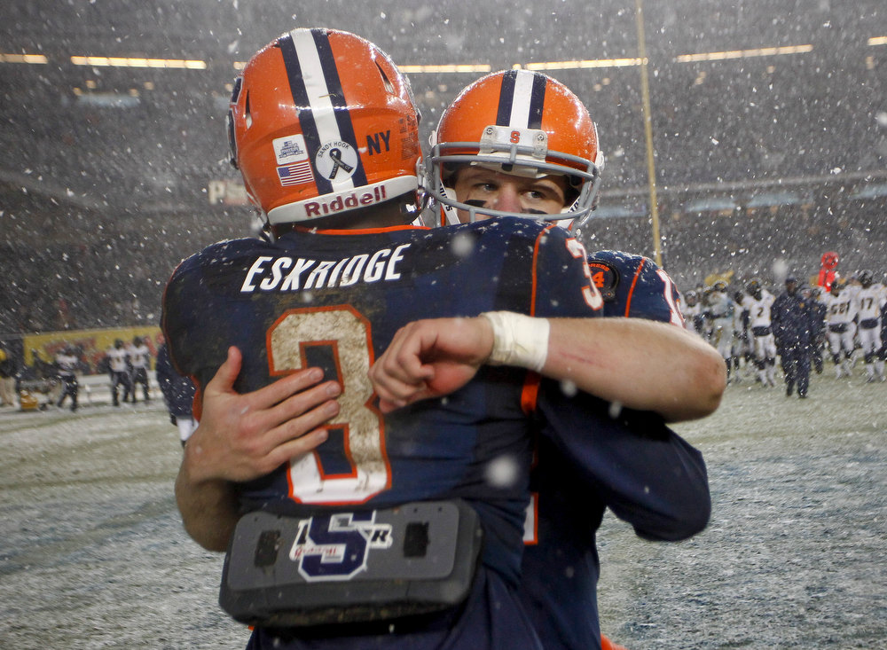 Description of . Ryan Nassib #12 and Durell Eskridge #3 of the Syracuse Orange celebrate victory over the West Virginia Mountaineers in the New Era Pinstripe Bowl at Yankee Stadium on December 29, 2012 in the Bronx borough of New York City.  (Photo by Jeff Zelevansky/Getty Images)