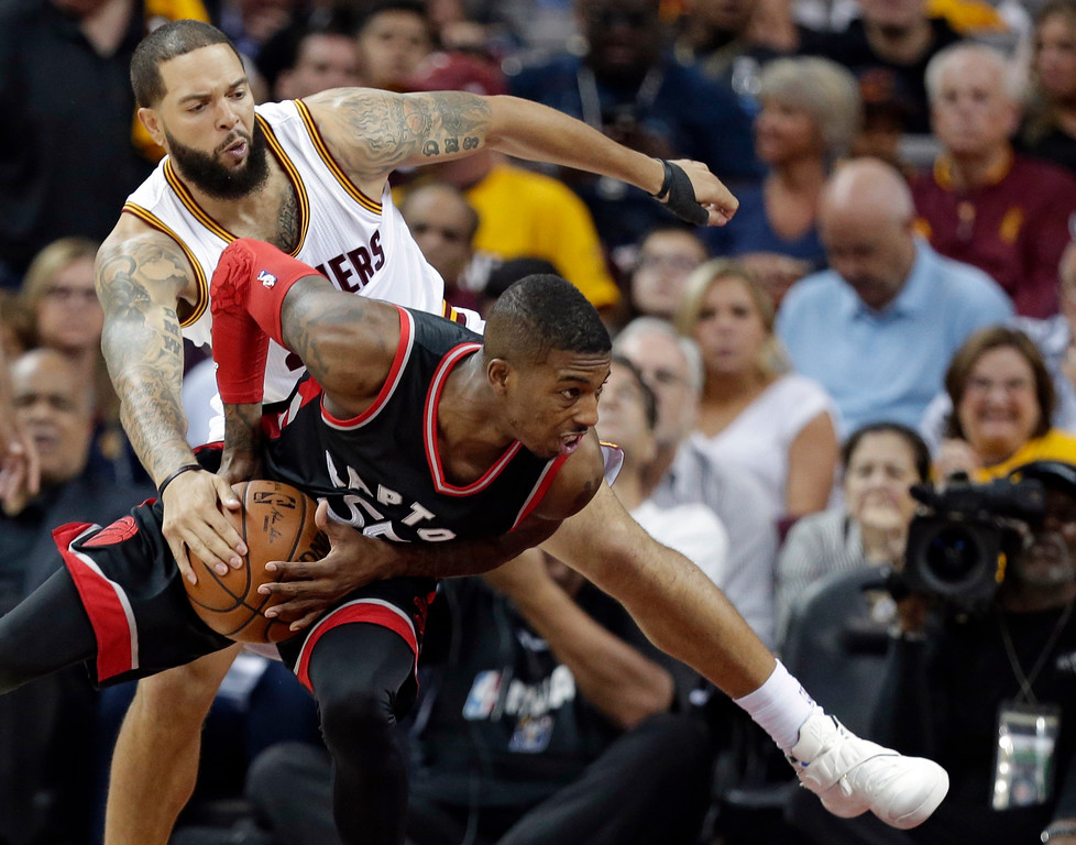 . Cleveland Cavaliers\' Deron Williams, back, fouls Toronto Raptors\' Delon Wright in the second half in Game 1 of a second-round NBA basketball playoff series,, Monday, May 1, 2017, in Cleveland. The Cavaliers won 116-105. (AP Photo/Tony Dejak)