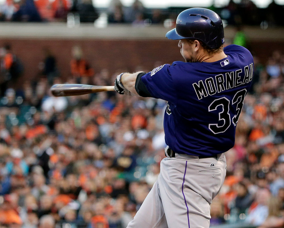 . Colorado Rockies\' Justin Morneau drives in a run with a sacrifice fly against the San Francisco Giants during the first inning of a baseball game Monday, Aug. 25, 2014, in San Francisco. (AP Photo/Marcio Jose Sanchez)
