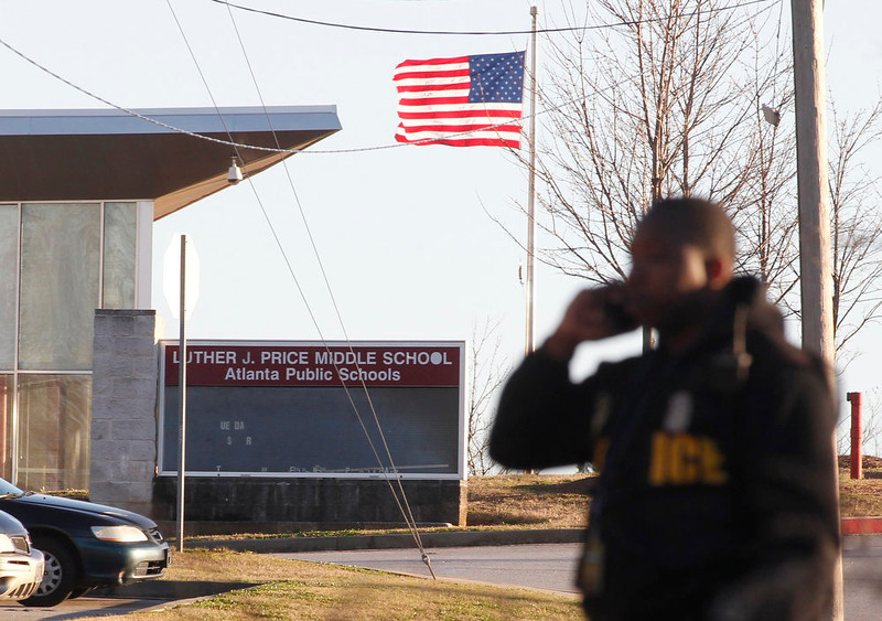 . An Atlanta policeman stands at the entrance to Price Middle School following a shooting at the school in Atlanta, Georgia, January 31, 2013.  One student was shot and another arrested in the latest string of school shootings.  REUTERS/Tami Chappell