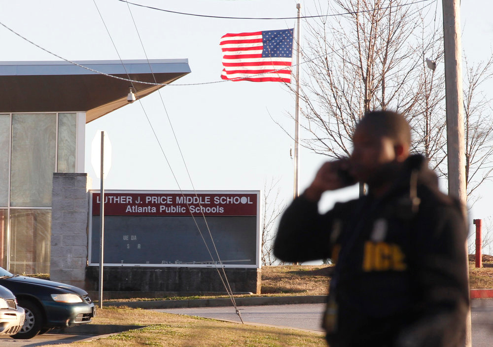 Description of . An Atlanta policeman stands at the entrance to Price Middle School following a shooting at the school in Atlanta, Georgia, January 31, 2013.  One student was shot and another arrested in the latest string of school shootings.  REUTERS/Tami Chappell