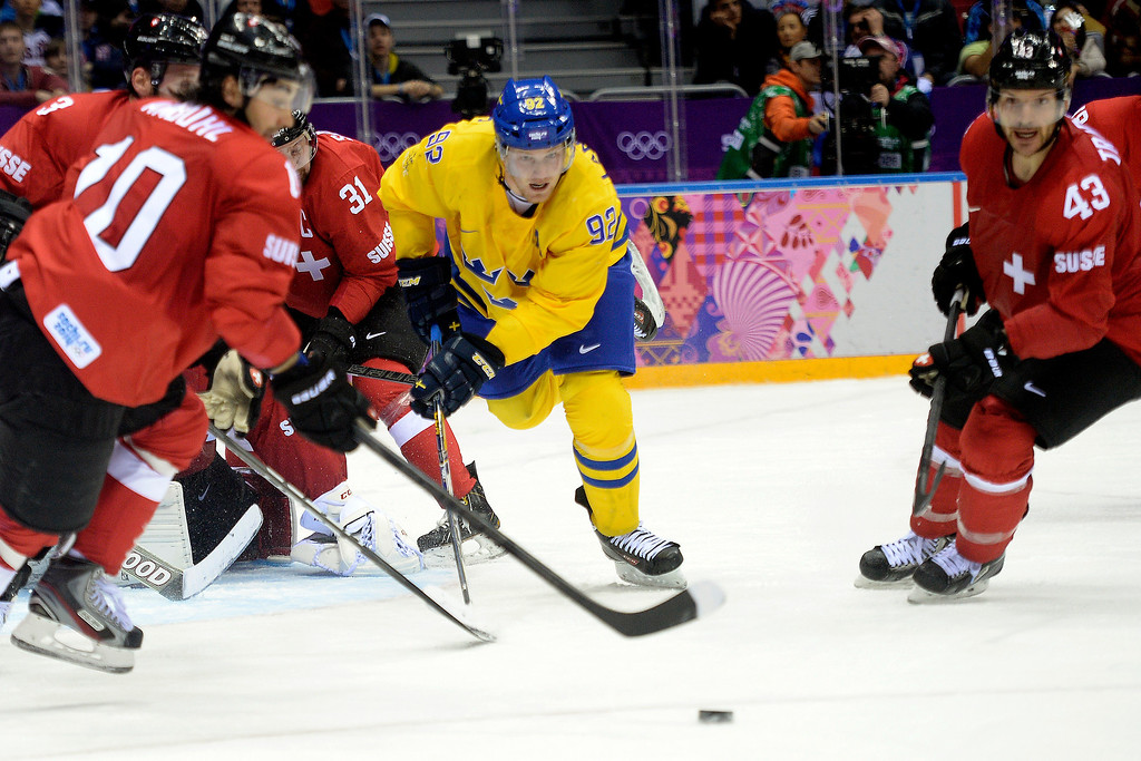 . Sweden\'s Gabriel Landeskog skates for the puck against a swarm of Switzerland defenders during the action at Bolshoy Arena. Sochi 2014 Winter Olympics on Friday, February 14, 2014. (Photo by AAron Ontiveroz/The Denver Post)