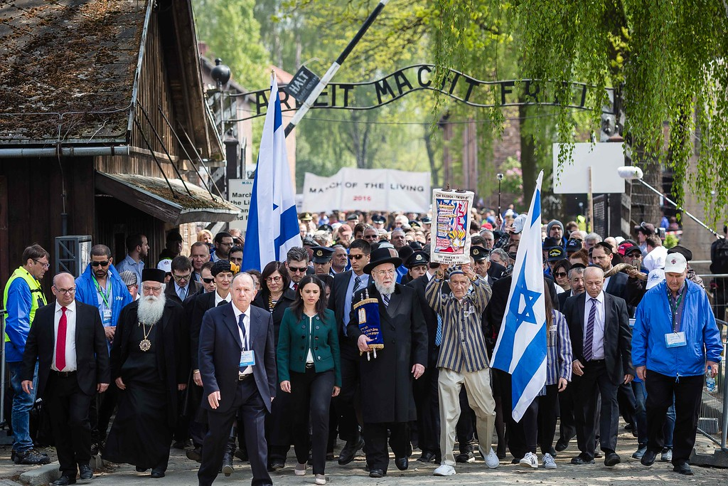 """. Participants of the annual \""""March of the Living\"""" are seen as they pass the main gate of the former Nazi death camp in Oswiecim (Auschwitz), Poland, on May 5, 2016. Thousands of young Jews from 40 nations marched alongside a handful of Holocaust survivors and Polish teenagers in homage to the victims of the former Auschwitz-Birkenau WWII death camp in southern Poland. / AFP PHOTO / WOJTEK RADWANSKI/AFP/Getty Images"""