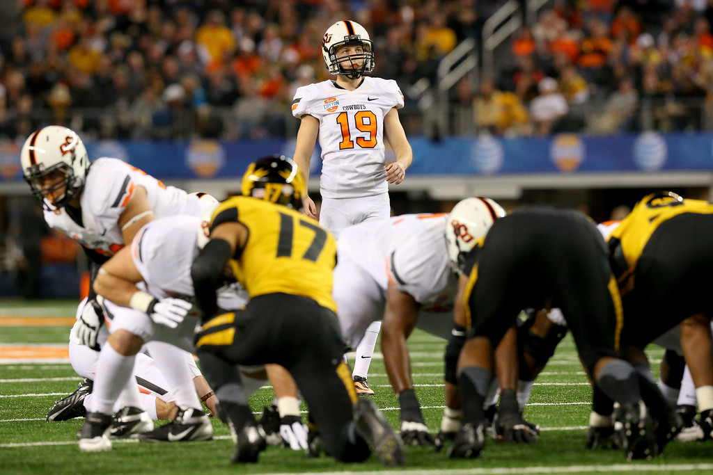 . ARLINGTON, TX - JANUARY 03:  Kicker Ben Grogan #19 of the Oklahoma State Cowboys looks up before he kicks against the Missouri Tigers in the first half during the AT&T Cotton Bowl on January 3, 2014 in Arlington, Texas.  (Photo by Ronald Martinez/Getty Images)