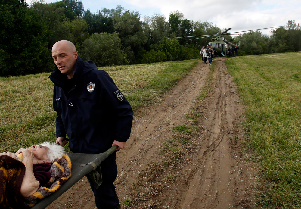. Serbian police officers carry an old woman out of military helicopter during flood evacuation from Obrenovac, some 30 kilometers (18 miles) southwest of Belgrade Serbia, Saturday, May 17, 2014. Record flooding in the Balkans leaves at least 20 people dead in Serbia and Bosnia and is forcing tens of thousands to flee their homes. Meteorologists say the flooding is the worst since records began 120 years ago. (AP Photo/Darko Vojinovic)