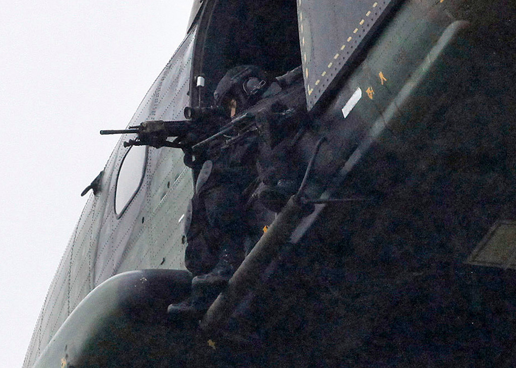 . Armed security forces fly overhead in a military helicopter  in Dammartin-en-Goele, northeast of Paris, Friday Jan. 9, 2015.   French security forces swarmed this small industrial town northeast of Paris Friday in an operation to capture a pair of heavily armed suspects in the deadly storming of a satirical newspaper. (AP Photo/Thibault Camus)