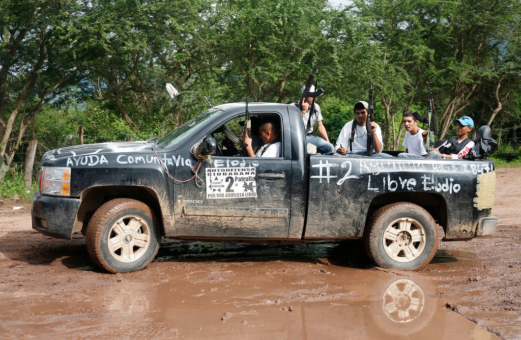 . Armed members of a recently formed self-defense group ride on a pickup truck at the entrance to the town of Aguililla, Mexico, Wednesday, July 24, 2013.  Mexico\'s rough western state of Michoacan is proving just as tough a thorn in the side of President Enrique Pena Nieto as it was for his predecessor after gunmen believed to be working for the Knights Templar cartel launched a coordinated series of a half-dozen ambushes on federal police convoys last Tuesday and another self-defense group has sprung up to fight against the Knights Templar.(AP Photo/Gustavo Aguado)