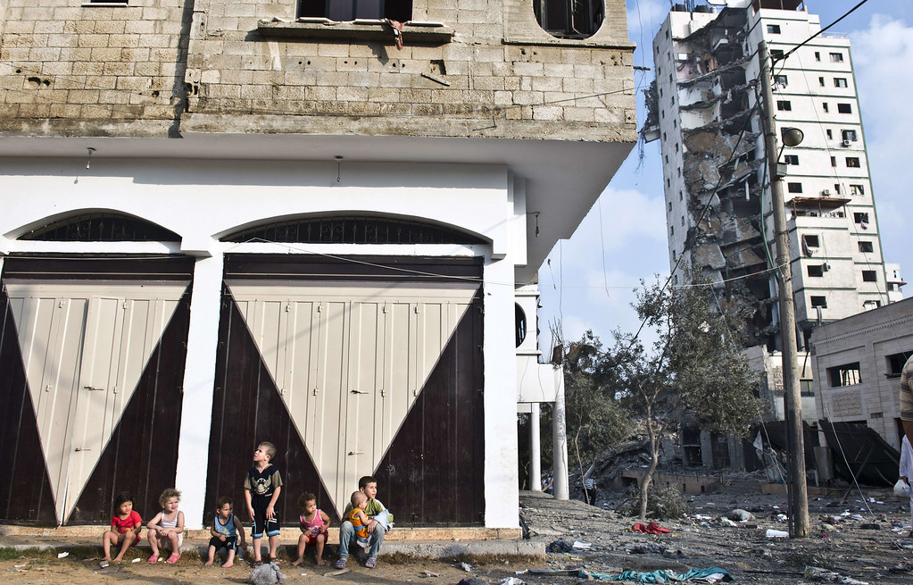 . Palestinian children sit on a sidewalk as they wait for their parents to retrieve some of their family\'s belongings from a partially destroyed house across the street from a high rise apartment building in Gaza City (R) that was targeted by Israeli airstrikes overnight on August 26, 2014.  The UN estimates that about a quarter of the 1.8 million inhabitants of Gaza have been displaced by fighting between Hamas militants and Israel since fighting started on July 8. ROBERTO SCHMIDT/AFP/Getty Images
