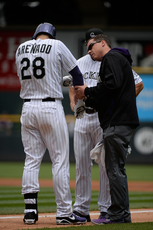 . DENVER, CO - MAY 22: Colorado Rockies trainer Keith Dugger takes a look at Colorado Rockies third baseman Nolan Arenado (28) after getting hit on the hand by a pitch from San Francisco Giants starting pitcher Tim Hudson (17) during the first inning May 22, 2014 at Coors Field. (Photo by John Leyba/The Denver Post)
