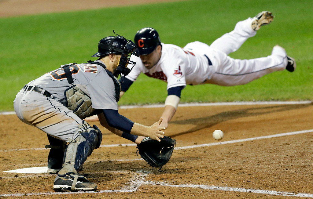 . Detroit Tigers\' Bryan Holaday, left, waits for the ball as Cleveland Indians\' Jason Kipnis slides safely into home plate on a double by Lonnie Chisenhall in the fourth inning of a baseball game, Wednesday, Sept. 3, 2014, in Cleveland. (AP Photo/Tony Dejak)