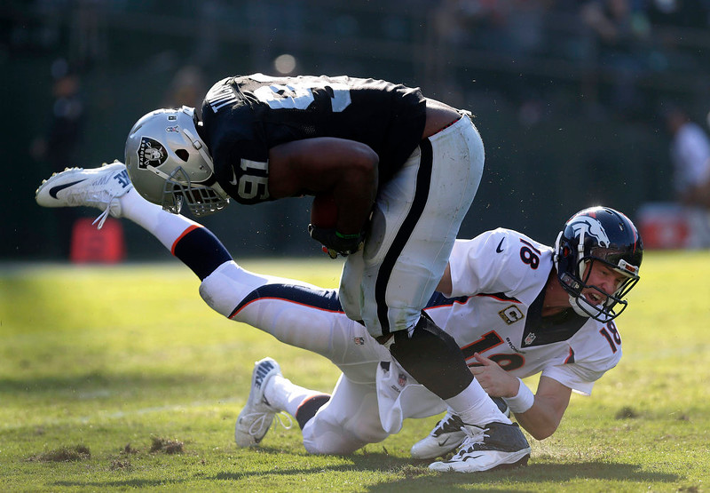 . Oakland Raiders defensive end Justin Tuck (91) runs past Denver Broncos quarterback Peyton Manning (18) after intercepting Manning during the second quarter of an NFL football game in Oakland, Calif., Sunday, Nov. 9, 2014. (AP Photo/Marcio Jose Sanchez)