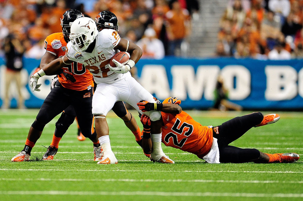 . Malcolm Brown #28 of the University of Texas Longhorns is brought down by Ryan Murphy #25 of the Oregon State Beavers during the Valero Alamo Bowl at the Alamodome on December 29, 2012 in San Antonio, Texas.  Texas won the game 31-27.  (Photo by Stacy Revere/Getty Images)