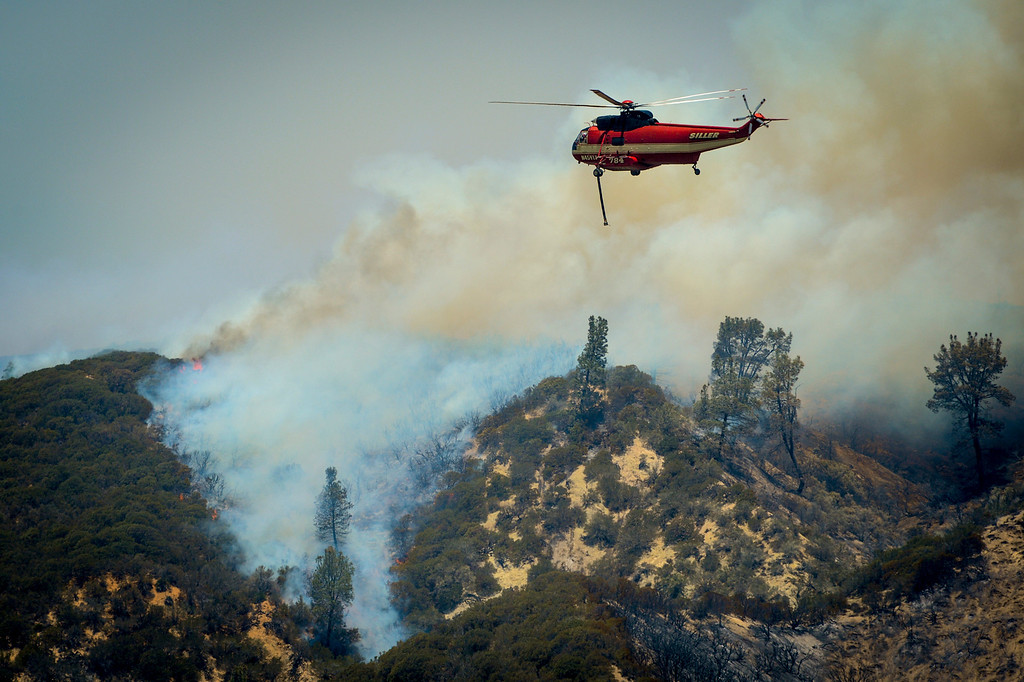 . A water dropping helicopter makes a run towards the Power House fire north of Lake Huges which continued to burn in an area mort of Santa Clarita Monday.   Photo by David Crane/Los Angeles Daily News