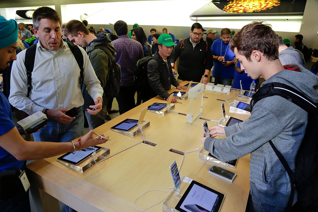 . Visitors to the Apple store examine the iPhone 6 and 6 Plus, Friday, Sept. 19, 2014,  in New York. The highly anticipated iPhone 6 and iPhone 6 Plus are being released in stores today. (AP Photo/Julie Jacobson)
