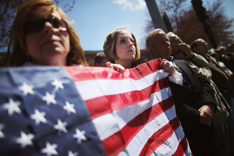 . Jaime Caputo (C) holds an American flag outside the funeral for 29-year-old Krystle Campbell, who was one of three people killed in the Boston Marathon bombings, on April 22, 2013 in Medford, Massachusetts. The 29-year-old restaurant manager was raised in Medford. Massachusetts Gov. Deval Patrick has asked residents to observe a moment of silence at the time of the first explosion at 2:50 p.m. this afternoon.  (Photo by Mario Tama/Getty Images)