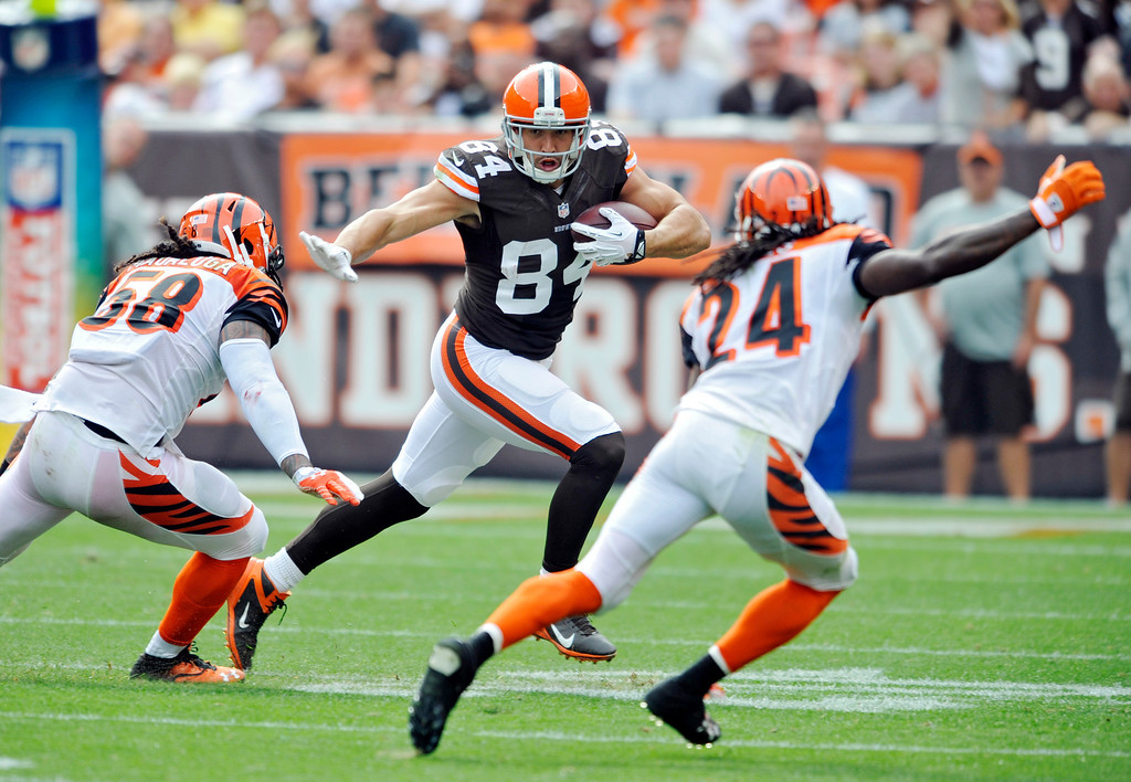 . Cleveland Browns tight end Jordan Cameron (84) runs after a catch against Cincinnati Bengals middle linebacker Rey Maualuga (58) and cornerback Adam Jones (24) in the second quarter of an NFL football game Sunday, Sept. 29, 2013, in Cleveland. (AP Photo/David Richard)