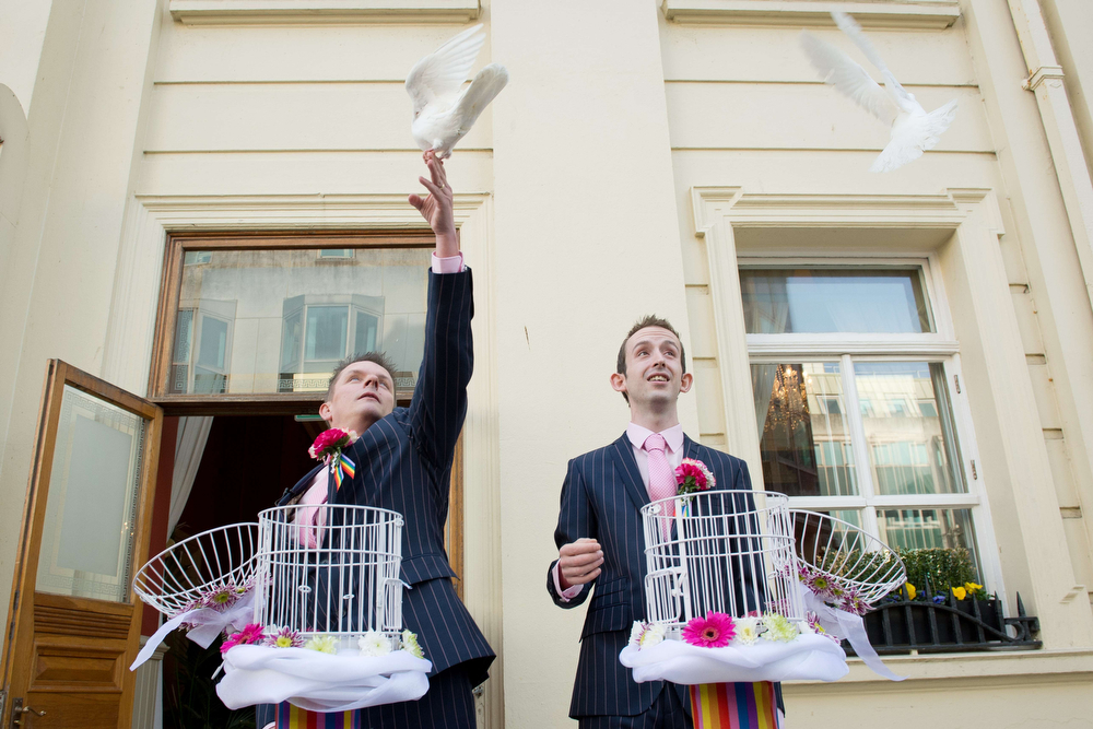 """. Phil Robathan (L) and James Preston (R) release doves following their wedding ceremony in Brighton, southern England, on March 29, 2014. Gay couples across England and Wales said \""""I do\"""" as a law legalizing same-sex marriage came into effect at midnight, the final stage in a long fight for equality.  (LEON NEAL/AFP/Getty Images)"""