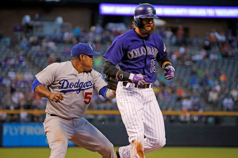. Los Angeles Dodgers third baseman Juan Uribe runs down and tags Colorado Rockies\' Charlie Blackmon (19) during the first inning of a baseball game Monday, Sept. 15, 2014, in Denver. (AP Photo/Jack Dempsey)